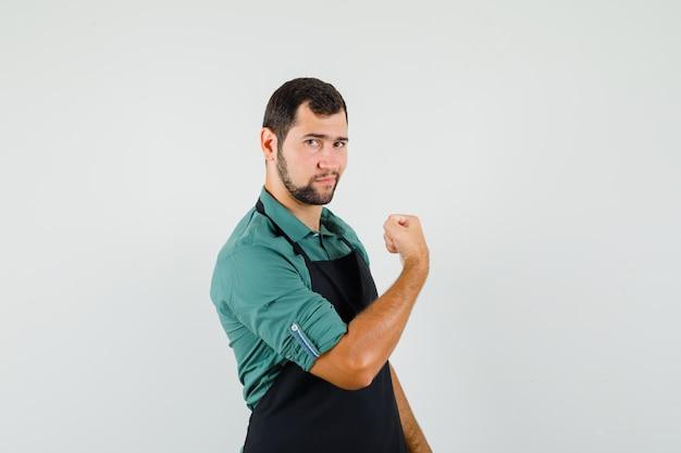 Молодой садовник показывает мышцы рук в футболке, фартуке и выглядит сильным. передний план.