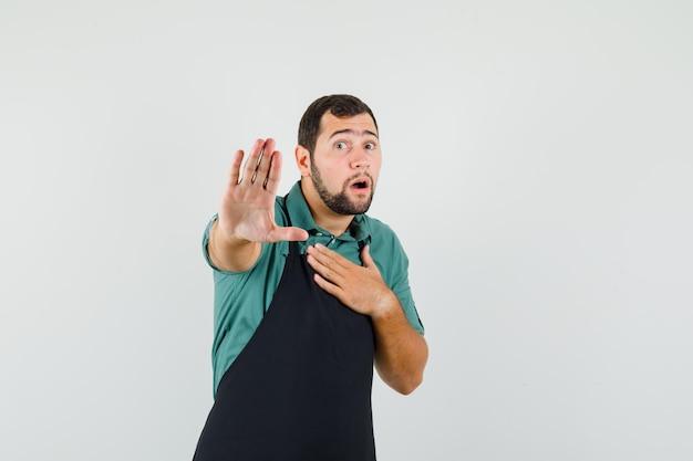 Giovane giardiniere che mostra il gesto di arresto mentre tiene la mano sul petto in maglietta, grembiule e sembra spaventato, vista frontale.