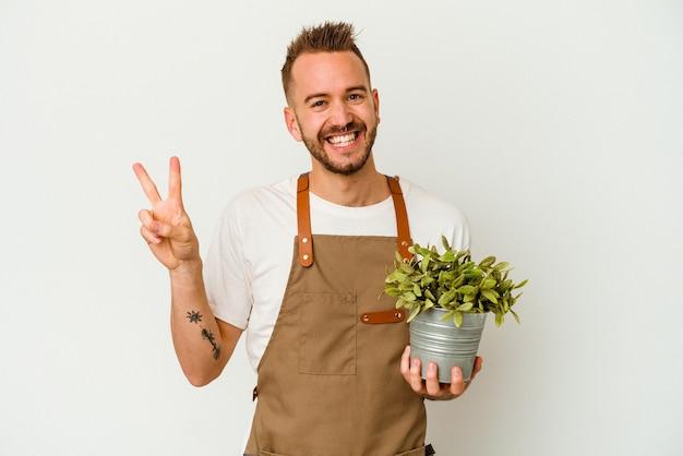 若い庭師は、白い背景に隔離された植物を持っている白人男性を入れ墨し、指で平和のシンボルを喜んで気楽に示しています。
