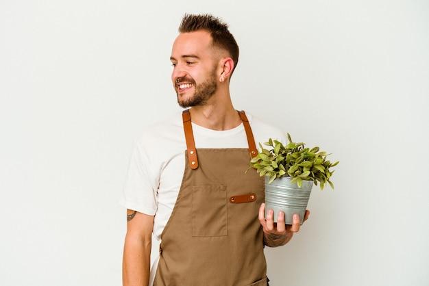 白い背景で隔離の植物を保持している若い庭師の入れ墨の白人男性は、笑顔、陽気で楽しい脇に見えます。