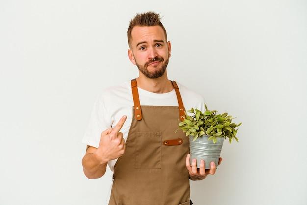 若い庭師は、招待が近づくようにあなたに指で指している白い背景で隔離された植物を保持している白人男性を入れ墨しました。
