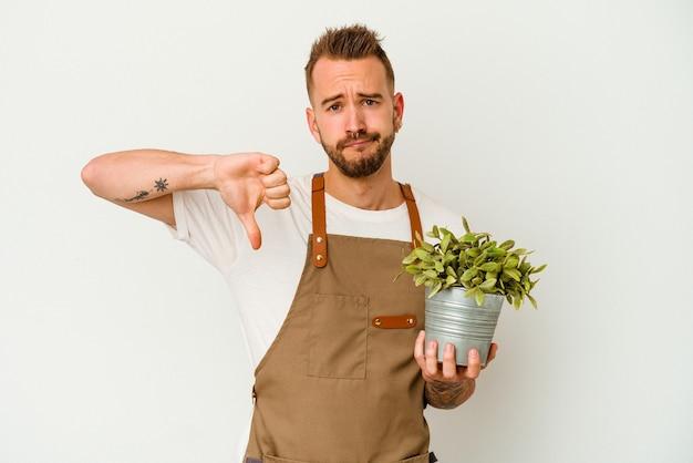 若い庭師は、嫌いなジェスチャーを示す白い背景で隔離された植物を保持している白人男性を刺青し、親指を下に向けます。不一致の概念。