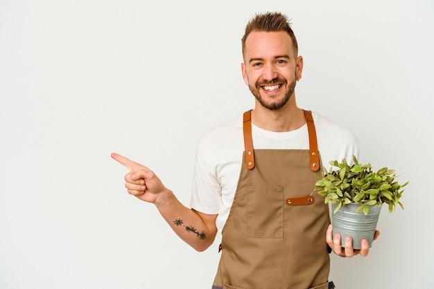 若い庭師は、白い背景に分離された植物を持って笑顔で脇を向いて、空白のスペースで何かを示している白人男性に入れ墨をしました。 Premium写真
