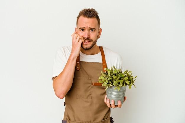 若い庭師は、白い壁に隔離された植物を持っている白人男性に刺青を入れ、爪を噛み、神経質で非常に心配しています。