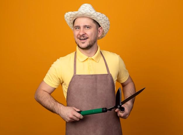 점프 슈트와 모자를 쓰고 젊은 정원사 오렌지 벽 위에 서있는 행복한 얼굴로 웃는 전면을보고 울타리 가위를 들고