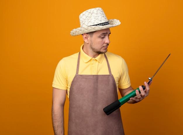 주황색 벽 위에 서있는 심각한 얼굴로보고있는 헤지 클리퍼를 들고 점프 슈트와 모자를 쓰고있는 젊은 정원사