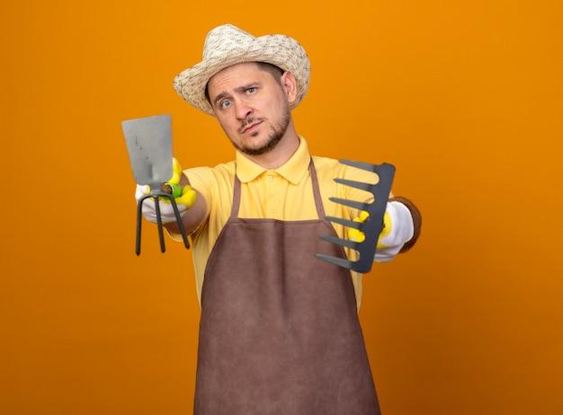 Молодой садовник в комбинезоне и шляпе держит мотыгу и мини-грабли, указывая с ними в камеру, уверенно смотрит в камеру, стоя над оранжевой стеной