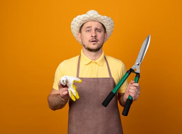 점프 슈트와 모자를 쓰고 젊은 정원사는 오렌지 벽 위에 서있는 자신감있는 표정으로 앞을보고 작업 장갑과 울타리 가위를 들고