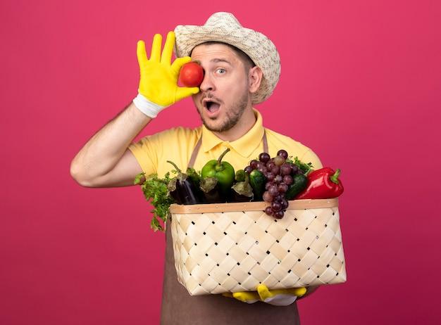 분홍색 벽 위에 서 놀란 찾고 그의 눈 위에 야채와 신선한 토마토로 가득한 상자를 들고 작업 장갑에 죄수 복과 모자를 착용하는 젊은 정원사