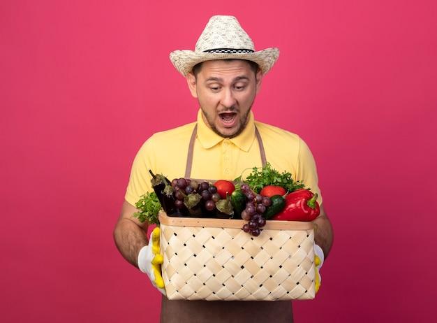 ピンクの壁の上に立って驚いて驚いたように見える野菜でいっぱいの木枠を保持している作業用手袋でジャンプスーツと帽子を身に着けている若い庭師