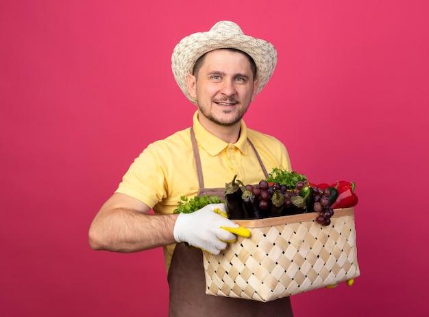 ピンクの壁の上に幸せで前向きに立って笑顔の正面を見て野菜でいっぱいの木枠を保持している作業手袋でジャンプスーツと帽子を身に着けている若い庭師