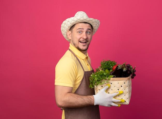 ピンクの壁の上に立って幸せそうな顔で笑顔で正面を見て野菜でいっぱいの木枠を保持している作業手袋でジャンプスーツと帽子を身に着けている若い庭師
