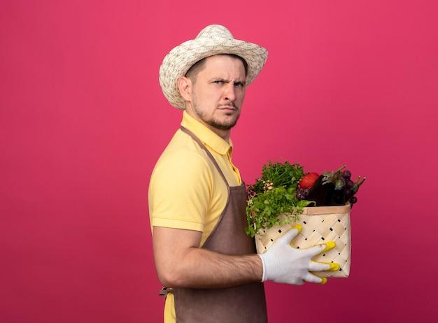 ピンクの壁の上に立っている深刻な顔のしかめっ面で正面を見て野菜でいっぱいの木枠を保持している作業用手袋でジャンプスーツと帽子を身に着けている若い庭師