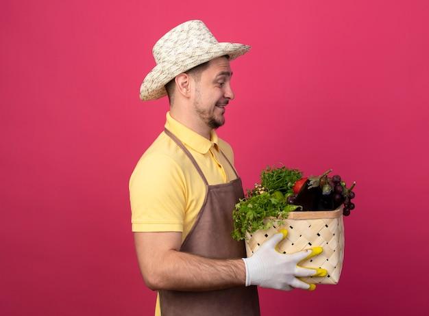 ピンクの壁の上に立って幸せで前向きに野菜を見ている野菜でいっぱいの木枠を保持している作業用手袋でジャンプスーツと帽子を身に着けている若い庭師