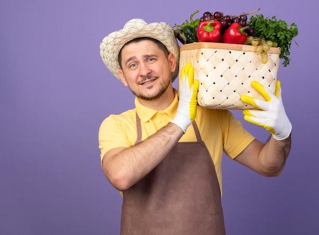 紫色の壁の上に立っている顔に笑顔で正面を見て肩に野菜でいっぱいの木枠を保持している作業用手袋でジャンプスーツと帽子を身に着けている若い庭師