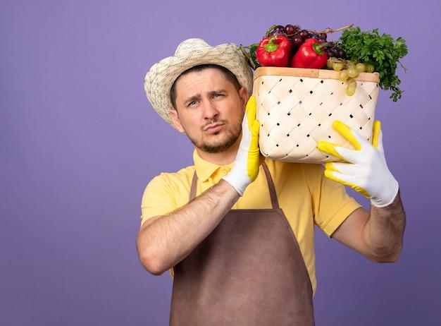 紫色の壁の上に自信を持って立っているように見える肩に野菜でいっぱいの木枠を保持している作業用手袋でジャンプスーツと帽子を身に着けている若い庭師