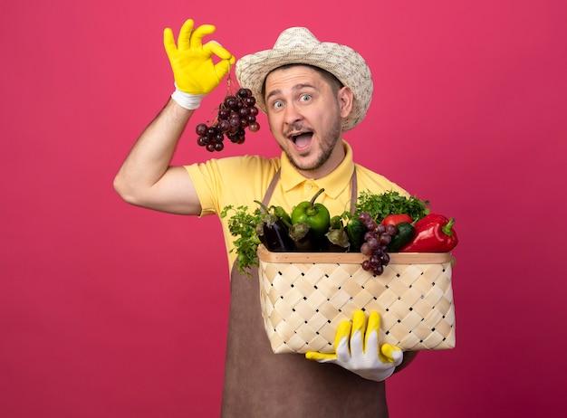 ピンクの壁の上に立って驚いた正面を見てブドウの束を示す野菜でいっぱいの木枠を保持している作業手袋でジャンプスーツと帽子を身に着けている若い庭師