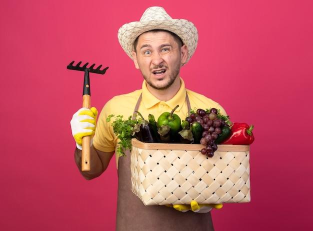 ピンクの壁の上に立って混乱している正面を見てミニ熊手を示す野菜でいっぱいの木枠を保持している作業手袋でジャンプスーツと帽子を身に着けている若い庭師