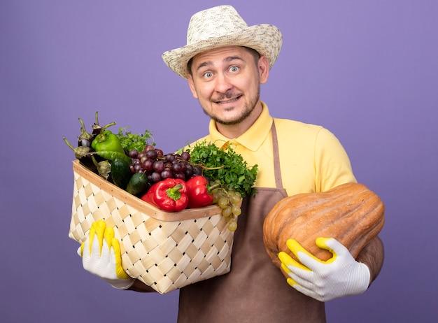 紫色の壁の上に立っている幸せそうな顔で笑顔で正面を見てカボチャと野菜でいっぱいの木枠を保持している作業手袋でジャンプスーツと帽子を身に着けている若い庭師