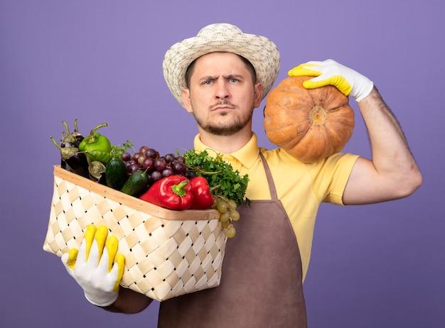 紫色の壁の上に立っている真面目な顔で正面を見てカボチャと野菜でいっぱいの木枠を保持している作業手袋でジャンプスーツと帽子を身に着けている若い庭師