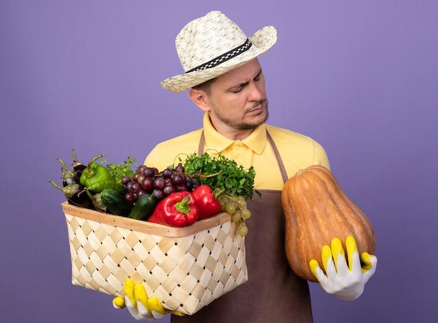 紫色の壁の上に立っている真面目な顔でそれを見てカボチャと野菜でいっぱいの木枠を保持している作業手袋でジャンプスーツと帽子を身に着けている若い庭師