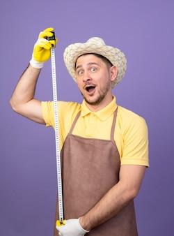 紫色の壁の上に立って幸せで驚きの正面を見てメジャーテープを保持している作業手袋でジャンプスーツと帽子を身に着けている若い庭師