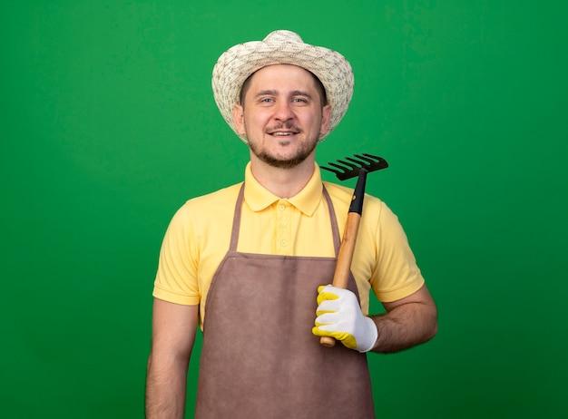 緑の壁の上に立っている顔に笑顔で正面を見てミニ熊手を保持している作業用手袋でジャンプスーツと帽子を身に着けている若い庭師