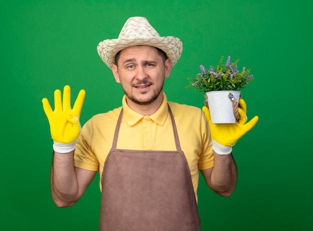 Молодой садовник в комбинезоне и шляпе в рабочих перчатках держит растение в горшке и смотрит вперед, показывая номер четыре, стоящий над зеленой стеной