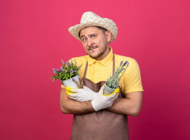 ピンクの壁の上に立って混乱して正面を見て鉢植えの植物を保持している作業用手袋でジャンプスーツと帽子を身に着けている若い庭師