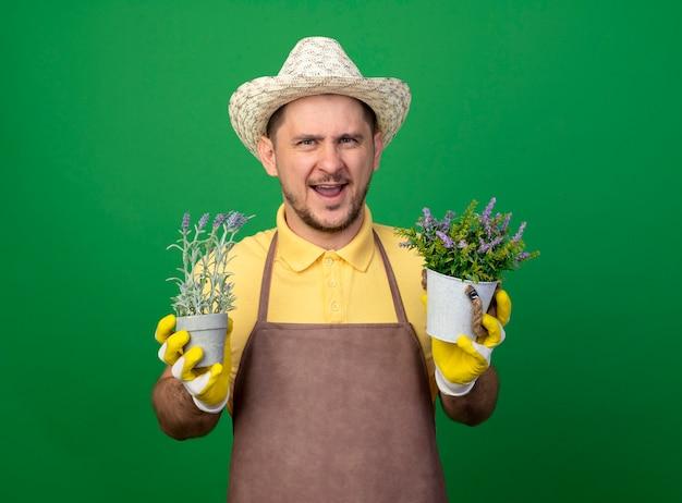 Молодой садовник в комбинезоне и шляпе в рабочих перчатках держит горшечные растения, глядя вперед, весело улыбаясь, стоя над зеленой стеной
