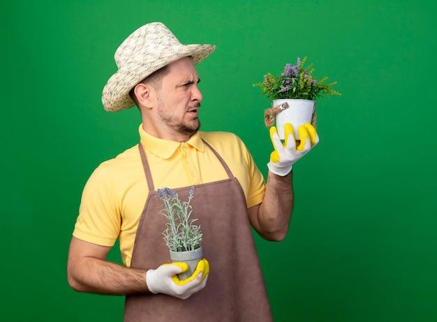 緑の壁の上に立って混乱し、不快になっている鉢植えの植物を見ている作業用手袋でジャンプスーツと帽子を身に着けている若い庭師