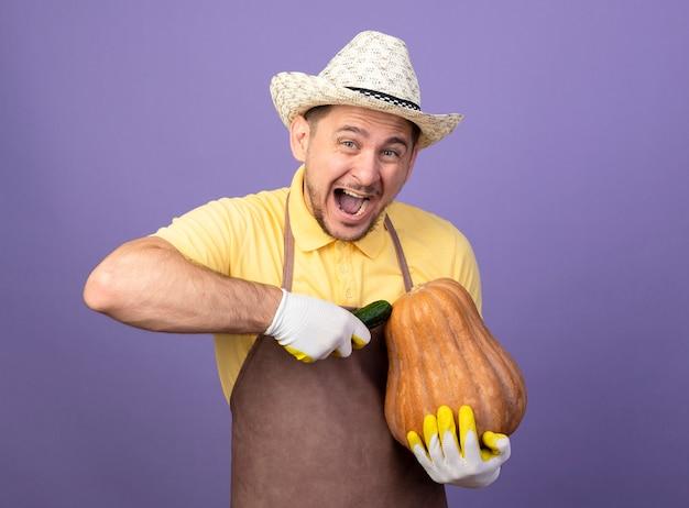紫色の壁の上に立って幸せで興奮してカボチャとキュウリを保持している作業手袋でジャンプスーツと帽子を身に着けている若い庭師