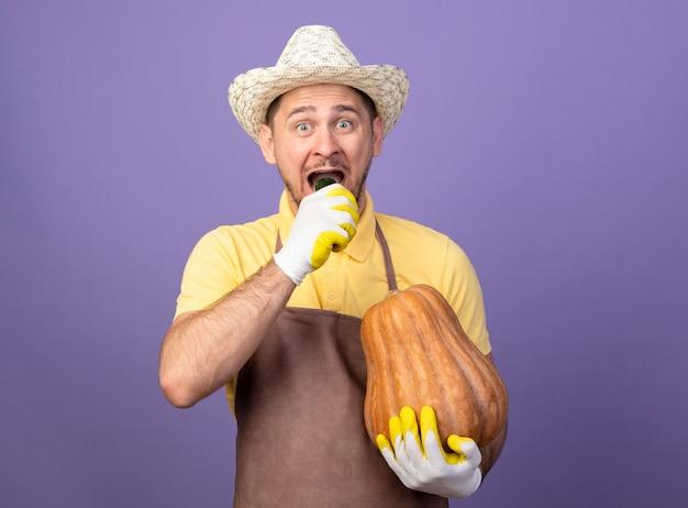 紫色の壁の上に幸せで前向きに立っているカボチャを噛んでキュウリを保持している作業手袋でジャンプスーツと帽子を身に着けている若い庭師