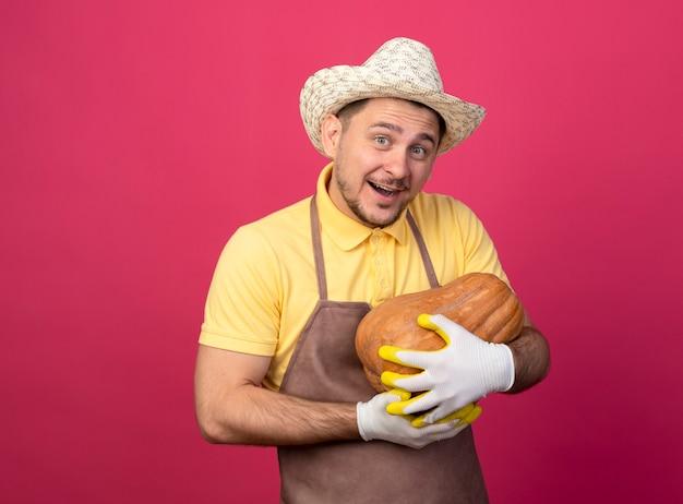Молодой садовник в комбинезоне и шляпе в рабочих перчатках держит тыкву, чувствуя положительные эмоции, улыбаясь, глядя вперед, стоя над розовой стеной