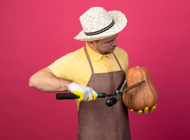 분홍색 벽 위에 서있는 울타리 가위를 사용하여 잘라가 호박을 들고 작업 장갑에 죄수 복과 모자를 착용하는 젊은 정원사