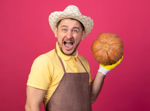 ピンクの壁の上に立って興奮して幸せそうな顔で笑顔で正面を見てカボチャを保持している作業手袋でジャンプスーツと帽子を身に着けている若い庭師