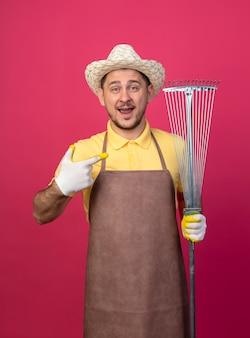 ピンクの壁の上に立っている幸せそうな顔で笑って人差し指で指しているレーキを保持している作業手袋でジャンプスーツと帽子を身に着けている若い庭師