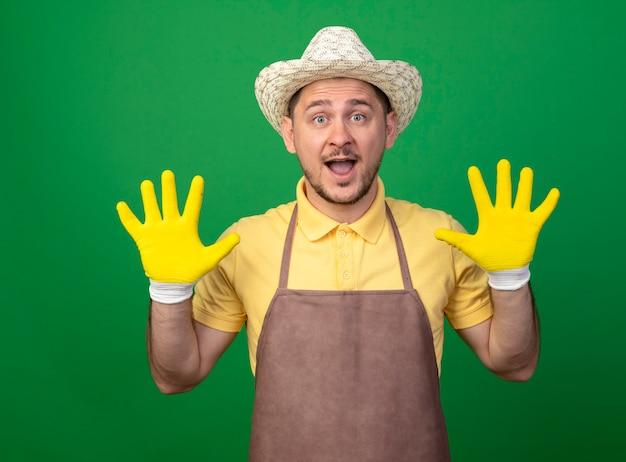Молодой садовник в комбинезоне и шляпе в рабочих перчатках показывает и показывает пальцами номер десять, счастливый и удивленный, стоя над зеленой стеной