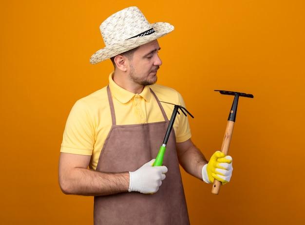 Giovane giardiniere che indossa tuta e cappello azienda mattock e mini rastrello guardandoli con faccia seria in piedi sopra la parete arancione