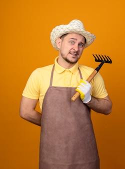 Giovane giardiniere che indossa tuta e cappello tenendo mini rastrello guardando davanti sorridente confuso in piedi sopra la parete arancione
