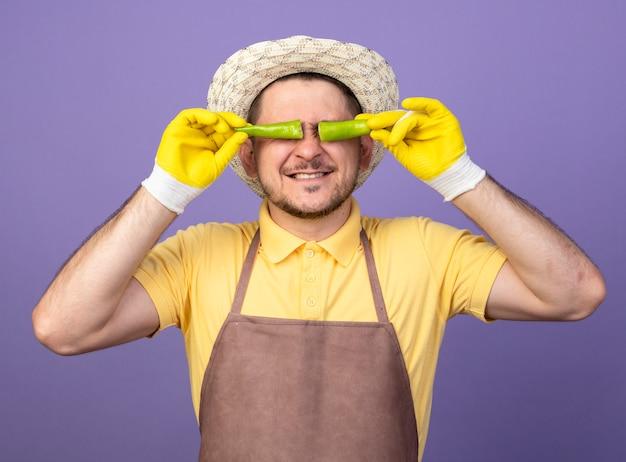 Giovane giardiniere che indossa tuta e cappello in guanti da lavoro in possesso di peperoncino verde rotto sopra gli occhi sorridenti in piedi sopra la parete viola