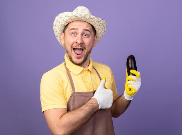 Giovane giardiniere che indossa tuta e cappello in guanti da lavoro in possesso di melanzane guardando la parte anteriore che mostra i pollici in su in piedi sul muro viola