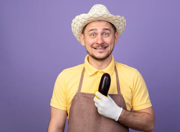 Giovane giardiniere che indossa tuta e cappello in guanti da lavoro in possesso di melanzane guardando davanti sorridente con la faccia felice in piedi sopra la parete viola