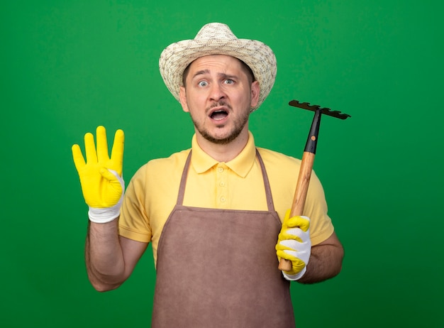 Young gardener wearing jumpsuit and hat in working gloves holding mini rake looking at front confused showing number four standing over green wall