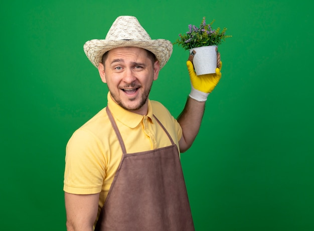 Young gardener wearing jumpsuit and hat in working gloves holding potted plant looking at front smiling with happy face standing over green wall