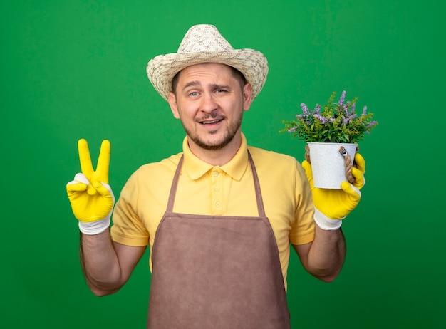 Giovane giardiniere che indossa tuta e cappello in guanti da lavoro che tengono pianta in vaso in piedi sopra la parete verde