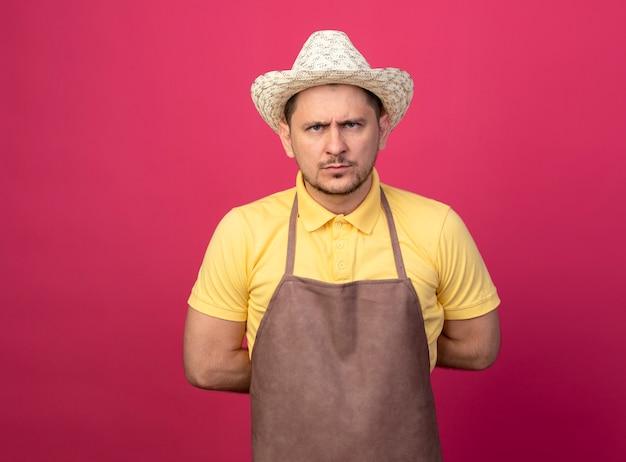 Giovane giardiniere che indossa tuta e cappello in guanti da lavoro guardando davanti con faccia seria dispiaciuta in piedi sopra il muro rosa