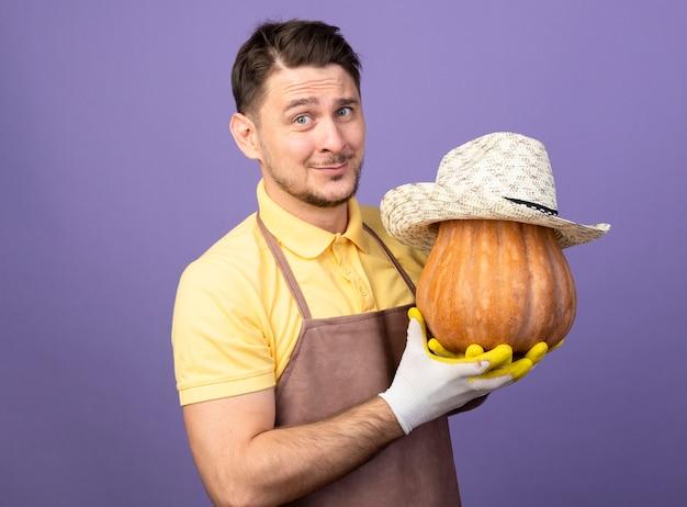 Giovane giardiniere che indossa la tuta in guanti da lavoro tenendo la zucca con il suo cappello guardando davanti sorridente con la faccia felice in piedi sopra la parete viola