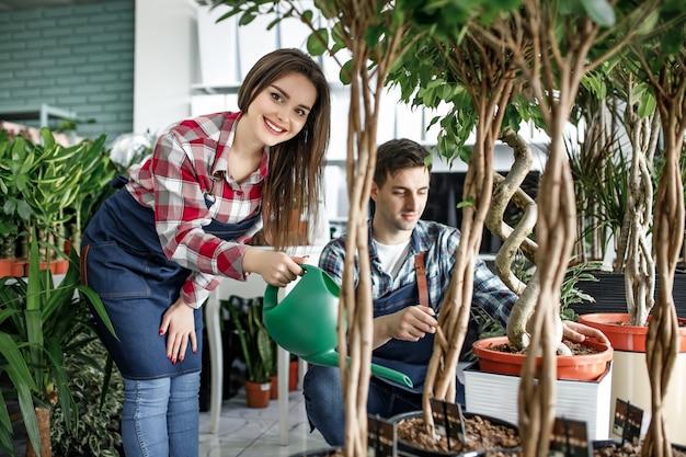Giovane donna giardiniere che assiste il maschio in un centro di piante e innaffia i fiori con un annaffiatoio