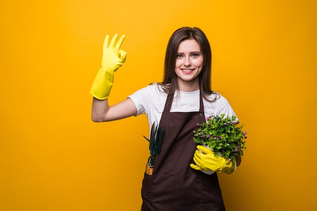 大丈夫なジェスチャーを与える植物を保持している若い庭師の女性